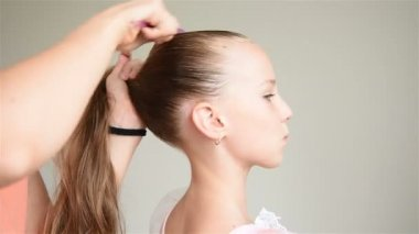 Assistant Does Hairdo For A Young Ballerina. Close Up