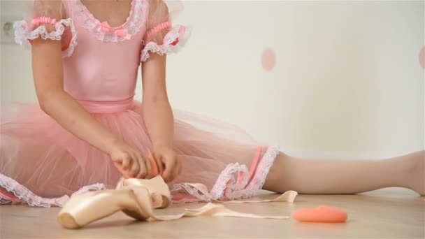 Ballerina Girl Sitting On Floor And Gathers Her Pointe