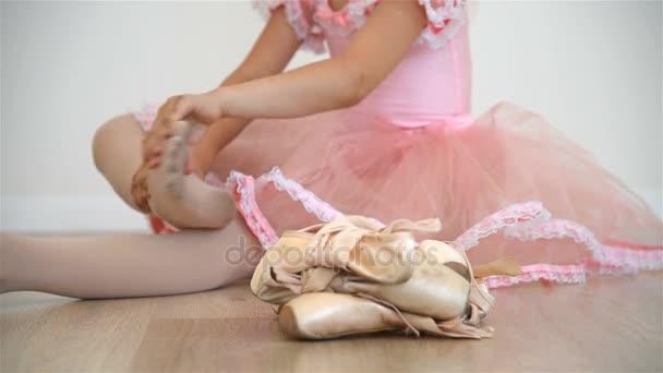 Llittle Ballerina Sitting On Floor In Dance Studio And Kneading His Legs