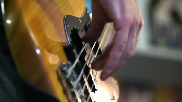 Hudebník hraje na basovou kytaru. Efekt zpomaleného pohybu