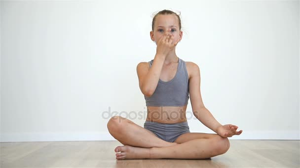 Malá holka sedí na podlaze v lotosové pozici a dělat dechová cvičení