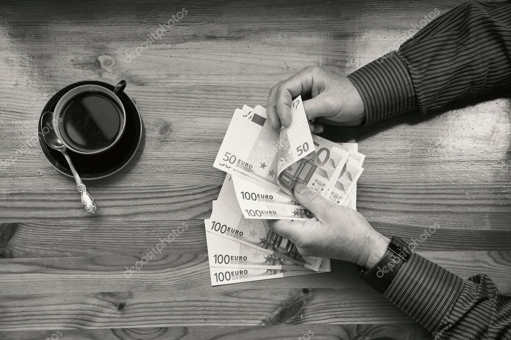 The rich man in shirt counting euro money and drinking coffee black and white photography a top view photo by devin pavel