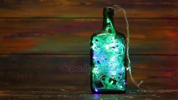 Vánoční ozdoby. Světelná girlanda v láhvi na dřevěné pozadí. Volné místo
