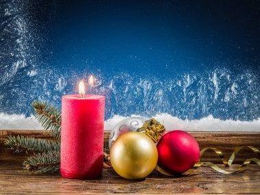 Christmas candle, Christmas balls and frozen window on backgroun