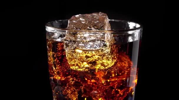 Üveg kóla és a jég a fekete háttér a saját tengelye körül forog. 4k videóinak.
