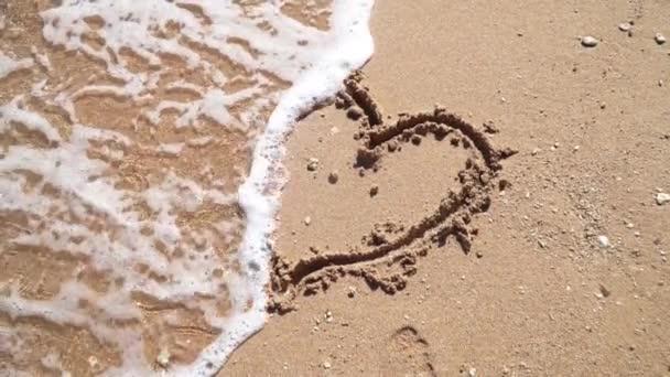 Moře na písku sweep vlny ve tvaru srdce. Zpomalený pohyb