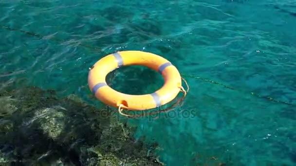 Orangefarbene Rettungsboje auf blauem Meer. Zeitlupe.