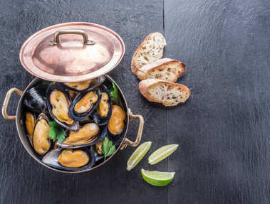 Mussels in copper pan on the graphite background.