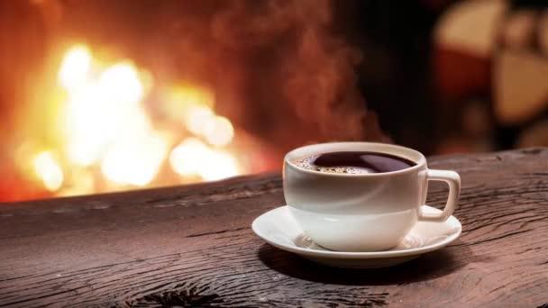 Csésze kávé áll egy régi fából készült fedélzet egy égő kandalló előtt. Steam emelkedik ki egy csésze kávét. A végtelenített videót 1920 x 1080