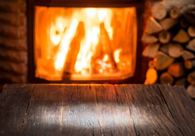 Empty wooden table and fireplace with warm fire at the backgroun