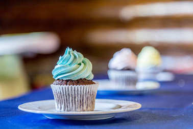 Tasty cupcake with blue butter cream on the white plate.