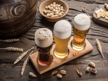 Glasses of beer and snacks on the wooden table.