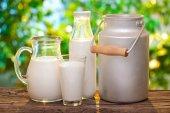 Farmě mléko v různých pokrmů na dřevěný stůl. Rozmazané eveni
