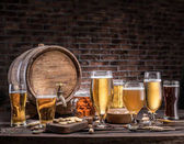Photo Glasses of beer and ale barrel on the wooden table. Craft brewer
