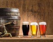 Sklenice piva a piva barel na dřevěný stůl. Brewe řemesla
