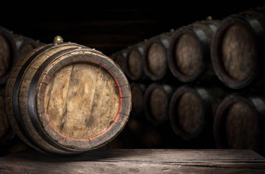 Wine barrel on the old wooden table. Wine cellar at the backgrou