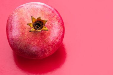 Ripe pomegranate fruit on the red background.