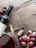 Fotografie Wine glass, wine bottle and grapes on wooden background. Wine ta