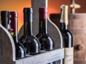 Láhve na víno v dřevěné bedně a dubový soudek vína