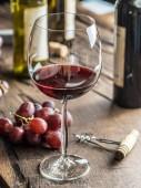 Bicchiere di vino rosso sul tavolo. Bottiglia di vino e luva a ba