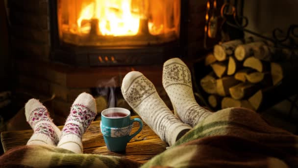 Warm atmosphere near the fireplace. Female and childrens feet in woolen socks, steam rises from a hot drink.
