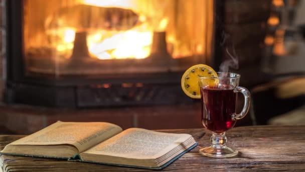 Teplá atmosféra u krbu. Horké svařené víno stojí na vinobraní stolu, pára stoupá z nápoje.