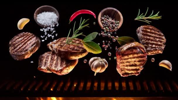 Smažené kousky hovězího steaku s kořením a solí visí nad grilem, uhlí pomalu hoří.