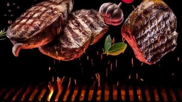 Grilované kousky steaku s kořením a solí pomalu padají na gril, uhlíky pomalu hoří.