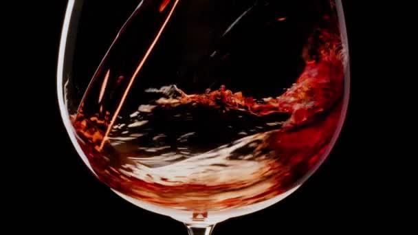 Červené víno se nalévá do sklenice na černém pozadí. Blízko. Černá magie 6k kamera.