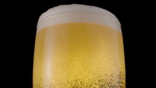 Sklenice světlého piva na černém pozadí. Bubliny a pěna pomalu stoupají na vrcholek sklenice s pivem. Otočení ve směru hodinových ručiček.