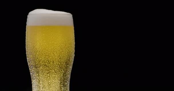 Egy pohár világos sör, fekete háttérrel. A repülő lassan megtölti az üveget sörrel, ami bőséges buborékokat és habot okoz. Az óramutató járásával megegyező irányba.