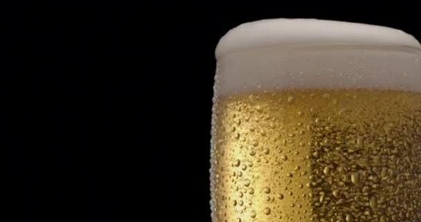Sklenice světlého piva na černém pozadí. Tryskáč pomalu naplňuje sklenici pivem, což způsobuje velké množství bublin a pěny. Otočení ve směru hodinových ručiček.