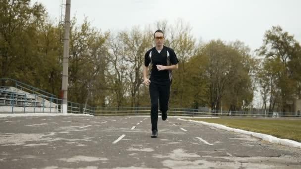 Atraktivní běžec v žluté sluneční brýle
