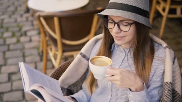 Lány élvezi a kávét, olvasás közben
