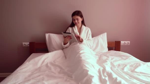 Žena v posteli s tabletem