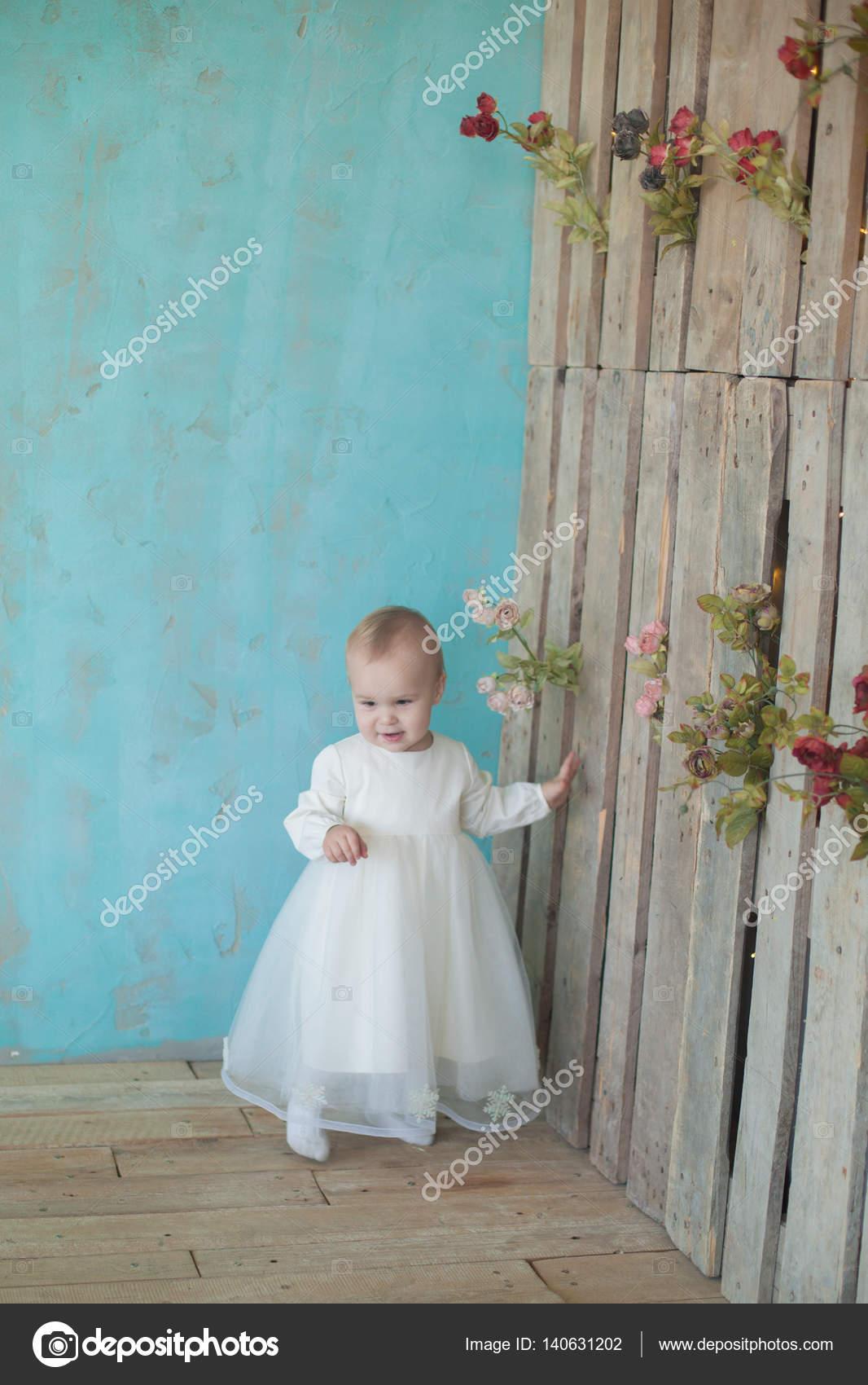 Muy linda rubia de niña pequeña con un vestido blanco en la ...