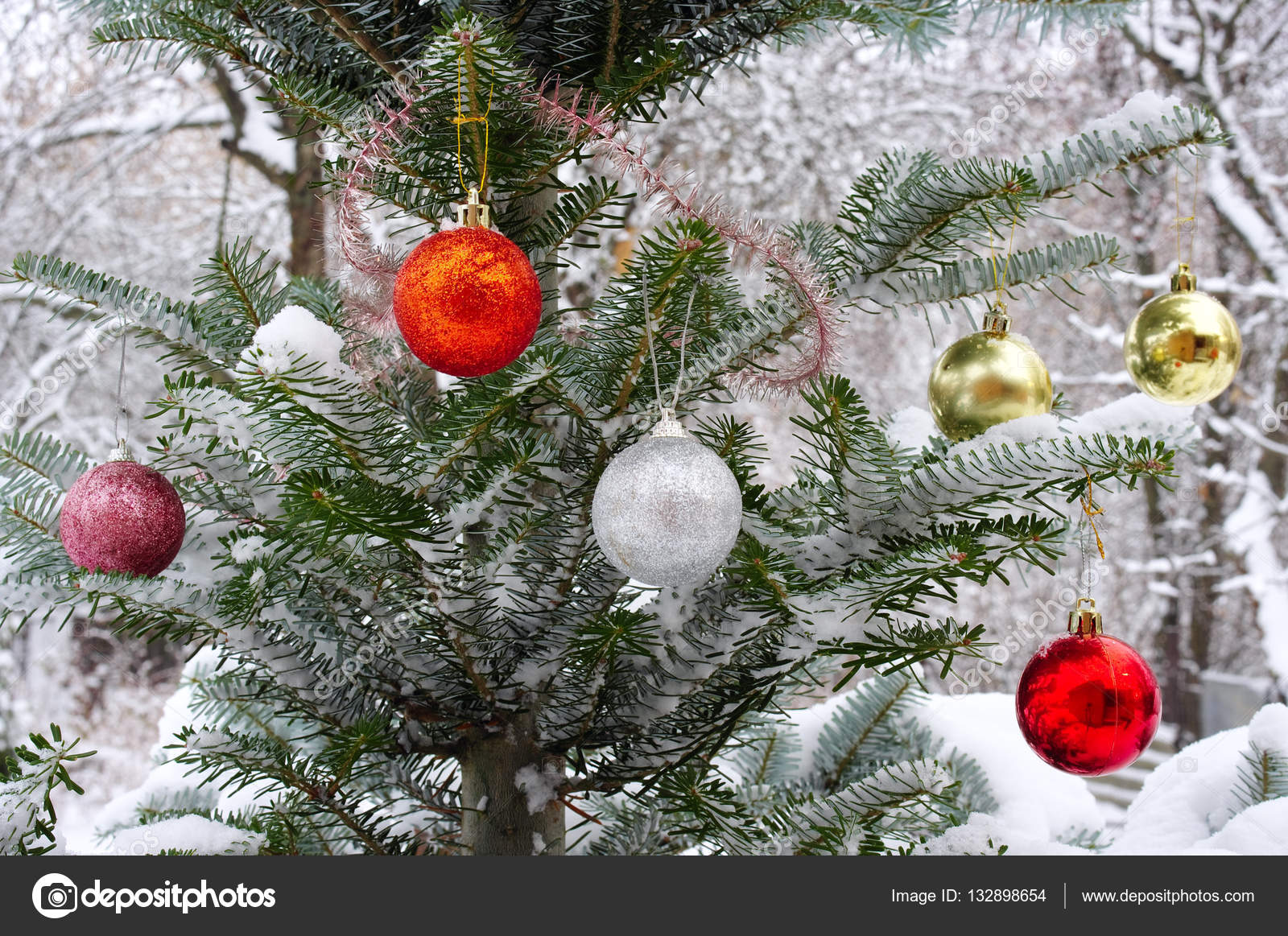 Christmas tree outside in the snow, decorated with Christmas toys– stock image