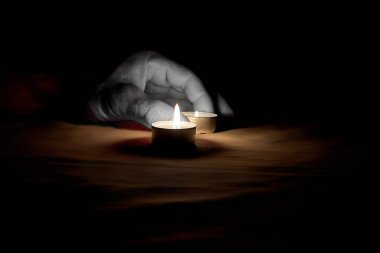 There is a memorable day on which a person puts a burning candle on the table next to a burning candle in the dark