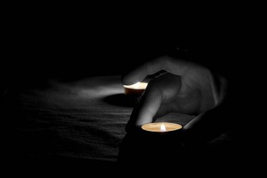 A man puts a burning candle on a colorless table next to a burning candle in the dark