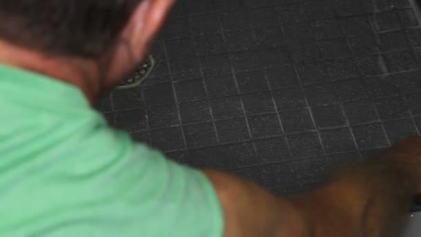 Muž drhnout podlahu sprchy