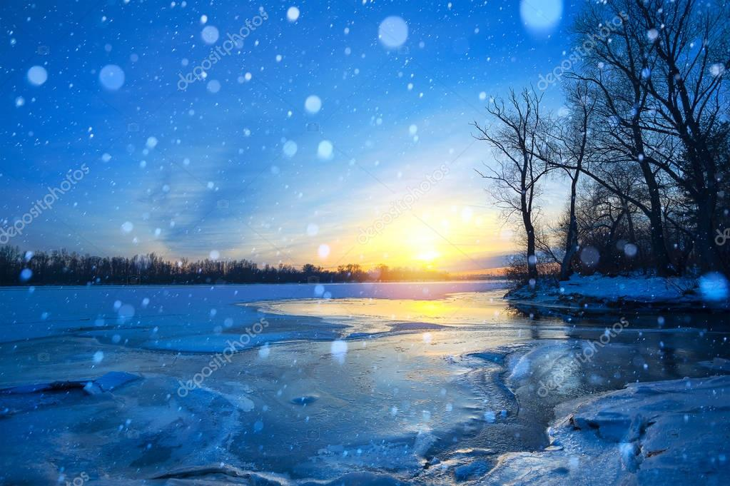 winter landscape panorama; sunset on the bank of a frozen river;