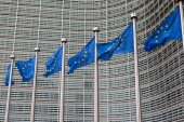 Row of EU European Union flags flying in front of administrative