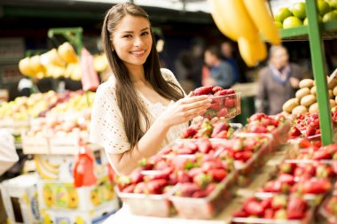 Young woman buying fruits at the market stock vector