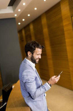 Modern businessman with phone in office