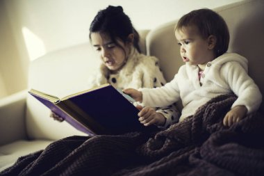 Cute little sisters reading a book