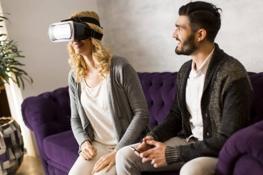 Woman with reality glasses while man sitting