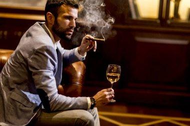 Man tasting wine and smoking cigar