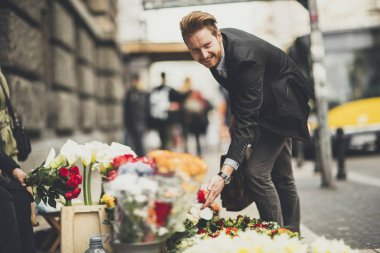 Man buys flowers from street vendors