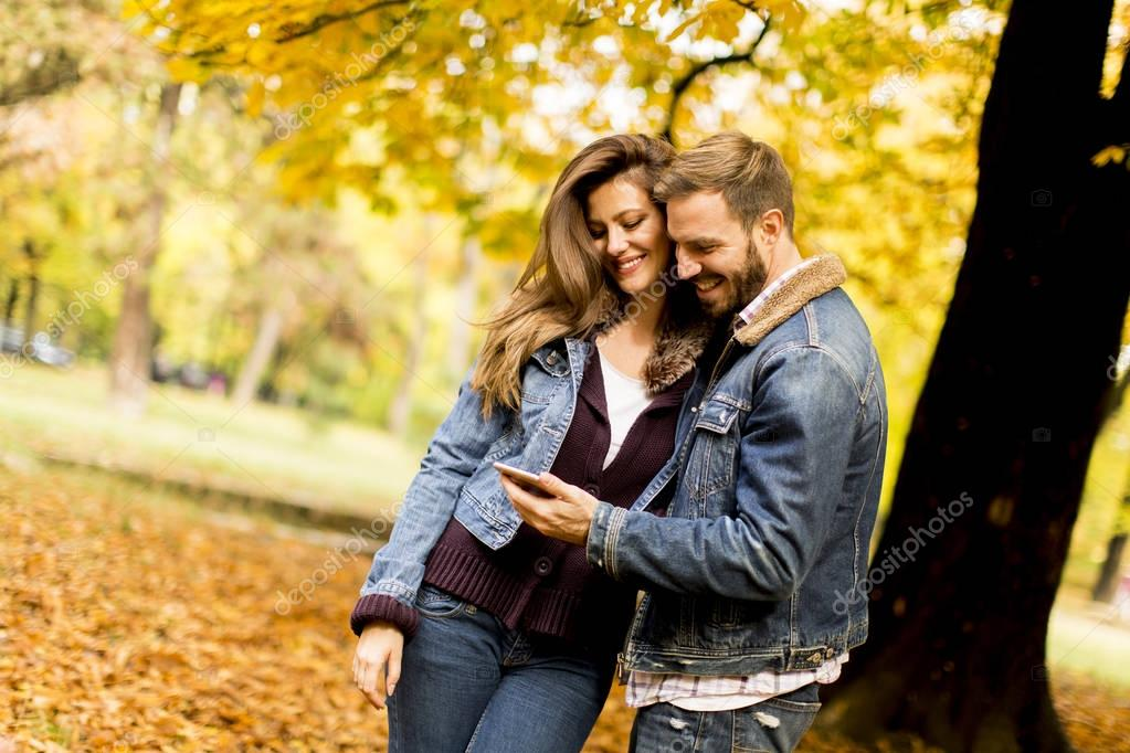 Happy couple watching a smart phone and standing in autumn park