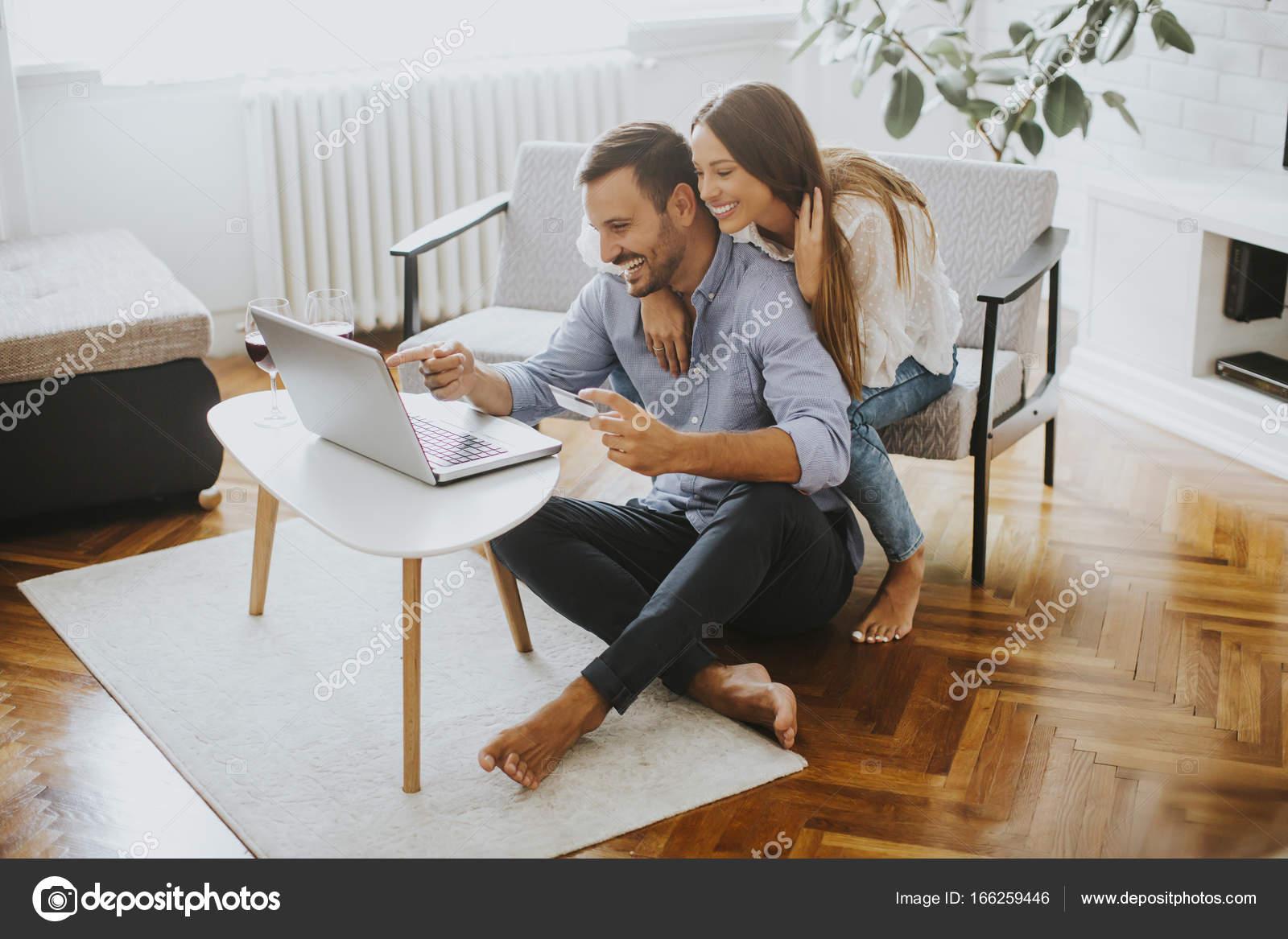 093f11ae29 Casal alegre, pesquisando a internet no laptop na sala de estar em casa —  Fotografia por boggy22